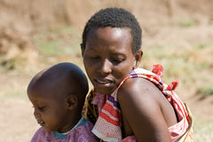 Maasai woman with her unidentified baby rest in the savannah. Royalty Free Stock Image