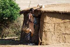 Maasai woman opens the entrance door. MASAI MARA, KENYA - JULY 12, 2010: Unidentified Maasai woman opens the entrance door of her mud built hut Stock Images