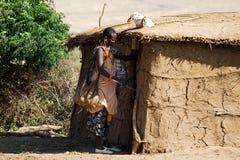 Maasai woman opens the entrance door. Stock Images