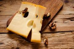 Maasdam乳酪用在一个黑暗的切板的核桃在年迈的木背景,上面竞争,选择聚焦 免版税图库摄影