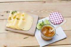Maasdam几个切片在木板,自创杏子果酱的乳酪 免版税库存图片