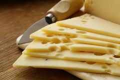Maasdam cheese sliced ​​on board Royalty Free Stock Images