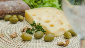 Maasdam cheese with white wine, olives and nuts stock footage