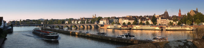 Maastricht, in the Netherlands. View across the Mass at the St. Servaasbrug bridge with a barge and the medieval town of Maastricht, in the Netherlands Stock Photos
