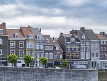 Beautiful old buildings along the Meuse River against a moody overcast sky in Maastricht, Netherlands royalty free stock photos