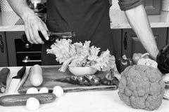 Maatregel nauwkeurig Niets sloopt schotel zoals een dubbel gedeelte van azijn of olie Handen van chef-kok mannelijke gietende sla stock foto's