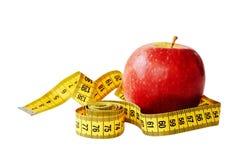 Maatregelenband en vers die fruitappel over witte achtergrond wordt geïsoleerd Verliesgewicht, slank lichaam, gezonde voedingconc stock afbeelding