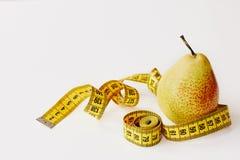 Maatregelenband en vers fruitpeer op witte achtergrond Verliesgewicht, slank lichaam, gezonde voedingconcept stock afbeeldingen