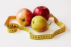 Maatregelenband en verse vruchten appelen, peer op witte achtergrond royalty-vrije stock foto