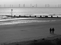 Mablethorpe beach in winter. Black and white shot of Mablethorpe beach in winter.Offshore windfarm and couple walking Royalty Free Stock Photography