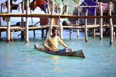 MABUL ISLAND, SABAH, MALAYSIA - MARCH 03 : Unidentified Sea Gyps. Ies boy paddles a boat on March 03, 2014 in Sabah, Malaysia. The Sea Gypsies are sea nomads Stock Images