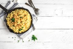 Mac and cheese baked pasta. Mac and cheese, american style macaroni pasta with cheesy sauce and crunchy breadcrumbs topping on white wooden table, copy space top stock images