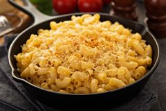 Mac and cheese in a cast iron pan. Baked with breadcrumbs with steamed broccoli stock photos