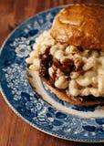 Mac och ostsmörgås med bringan och bbq-sås på en blå vin Arkivfoto