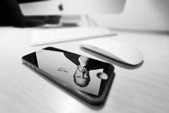 Mac with reflection of Steve Jobs in a iPhone 5. STOCKHOLM - APRIL 6: Mac with reflection of Steve Jobs in a iPhone 5 on table in room in black and white. April Stock Photos