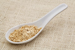 Maca root powder on a ceramic spoon. Ceramic tablespoon of maca root powder (dietetary supplement) against burlap canvas Royalty Free Stock Photography