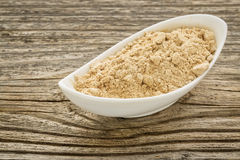 Maca root powder i. N a small ceramic bowl against grained wood Stock Photo