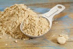 Maca root powder. A measuring tablespoon and pile on wooden surface Royalty Free Stock Photography