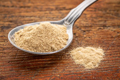 Maca root powder on tablespoon. Maca root powder on a tablespoon against rustic wood - superfood supplement concept Stock Photography
