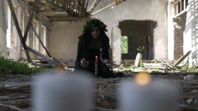 Macabre молодая ведьма проклиная и кладя произношения по буквам в церемонию с свечами в загубленном замке акции видеоматериалы