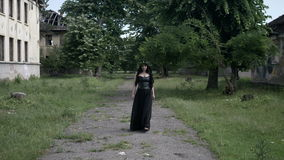 Macabre woman with gothic black clothes and crown of ivy leaves walking among ruined buildings with evil expression face. Young macabre woman with gothic black stock footage