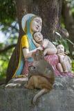 Macaco de Macaque com um bebê ao lado de uma estátua de Madonna e das crianças em Rishikesh, Índia fotografia de stock royalty free