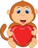 Macaco dos desenhos animados que guarda o coração vermelho Fotografia de Stock