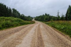 Macadam country road trough the forest. Country macadam road trough the forest, cloudy sky Royalty Free Stock Photography