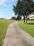 Macadam path by a golf course. Macadam path or walkway by a large grass area and trees Stock Images