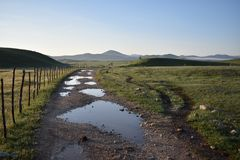 The macadam road dotted with the puddles and the mountains at the background. Montenegro Royalty Free Stock Photography