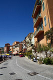 Macadam road with houses and restaurants in Villefranche Sur Meer in France. Vertical photo of macadam road with houses and restaurants in Villefranche Sur Meer Royalty Free Stock Photo