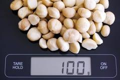 Macadamia καρύδια στην ψηφιακή κλίμακα Στοκ φωτογραφία με δικαίωμα ελεύθερης χρήσης