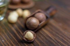 Macadamia dokrętki w drewnianej miarce nad zmroku stołem Zdjęcie Stock