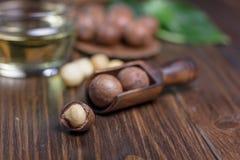Macadamia dokrętki w drewnianej miarce nad zmroku stołem Obrazy Stock