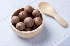 Macadamia in houten kom op witte houten lijst Stock Afbeelding