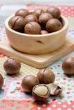 Macadamia on napery and wooden bowl Stock Photos
