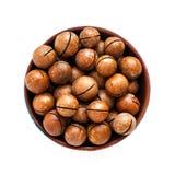 Macadamia noten in kom op witte achtergrond stock fotografie
