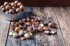 Macadamia noten met shells in een kom stock foto