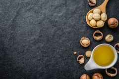 The Macadamia Nut Oil and peeled macadamia nut. Macadamia Nut Oil and peeled macadamia nut on black stone , use for Healthy Skin and Hair and Natural royalty free stock photos