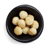 Macadamia Nuts in Black Bowl Overhead View Isolated on White Stock Photo