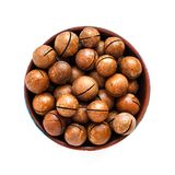Macadamia nuts in bowl on white background stock photography