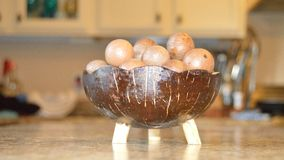 Macadamia nuts in a coconut bowl. On kitchen counter Stock Photo