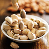 Macadamia nuts falling into bowl Royalty Free Stock Photography