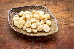 Macadamia nuts on leaf bowl Stock Photos
