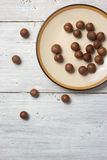 Macadamia nuts at the plate on the white background Royalty Free Stock Image