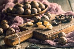 Macadamia nuts on table. Macadamia nuts on cutting board over wooden table Royalty Free Stock Images