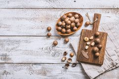 Macadamia nuts on table. Macadamia nuts on cutting board over white wooden table, top view Royalty Free Stock Photos