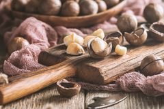 Macadamia nuts on table. Macadamia nuts on cutting board over wooden table Royalty Free Stock Photo