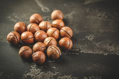 Macadamia nuts on wooden table royalty free stock photography
