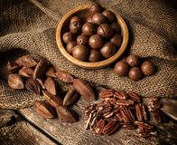 Macadamia, Pecan and Pili nuts on wooden table.  royalty free stock images